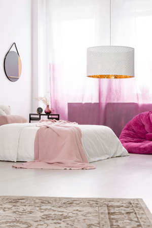 Pastel pink blanket thrown on the bed standing in bright stylish bedroom interior with white lamp