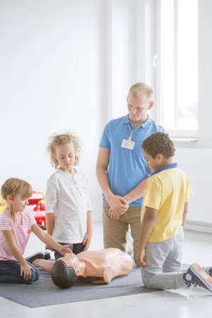 Kids learning how to open someones airway in emergency situation on a medical mannikin Stock Photo