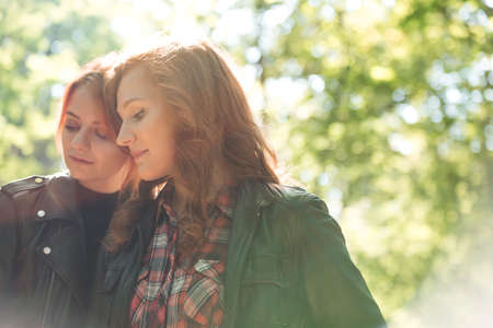 Filter of happy red-haired sisters enjoying a walk in the forest