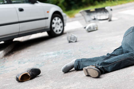 Fatal car accident involving a pedestrian. Drunk driver victim lying on the street 스톡 콘텐츠
