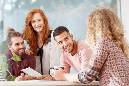 Multicultural group of co-workers smiling during an appointment with boss in the office Stock Photo
