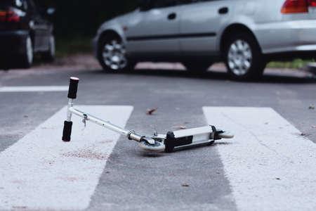 횡단 보도에 스쿠터의 근접입니다. 도로상의 어린이 안전 문제 스톡 콘텐츠