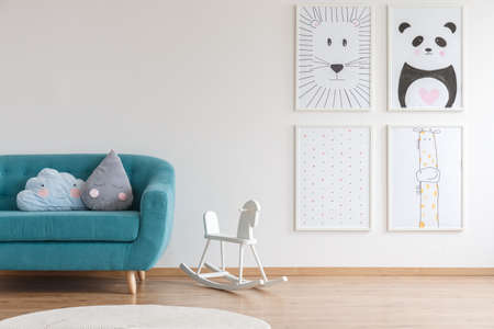 White rocking horse for children standing next to turquoise couch in interior with four posters Stock Photo - 96559024