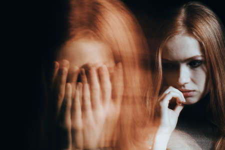 Close-up of a blurred face of a young girl with split personality disorder against black background Stock Photo - 96559028
