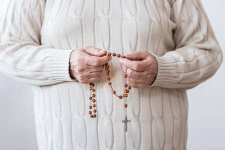 Close-up of religious person with red rosary praying in the church