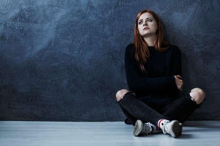 コピースペースで暗い背景に対して床に座っている失われた十代の女の子 写真素材
