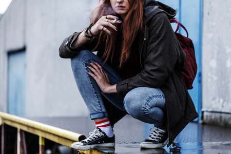 Close-up of teenage girl playing truant and smoking a cigarette on the sidewalk Stock Photo