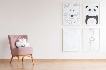 Pink armchair with cloud shaped toy standing in baby room with simple posters on empty wall Reklamní fotografie