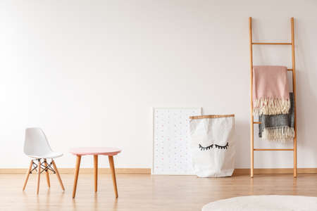 White chair and pink wooden table standing in baby room with material basket, blankets hanging on ladder and poster with dots Stock Photo