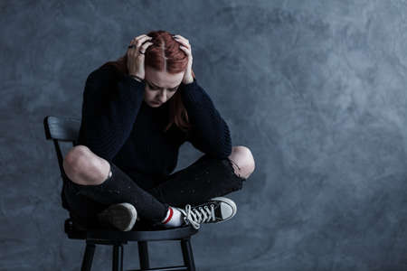 Worried teenager with a headache against dark background with copy space Imagens