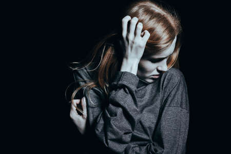 Young woman standing alone in a dark room at night trying to shake off a nightmare Stock Photo - 96558839