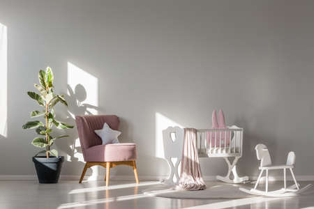 Monochromatic kid room interior with white cradle between a rocking horse toy and pink armchair