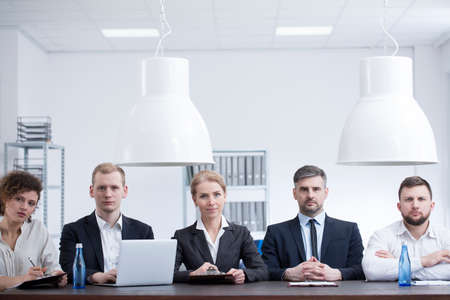 Businesswomen and businessmen in black suits sitting at a desk in a corporate office during a meeting