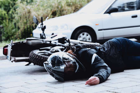 Dead motorcyclist lying next to her motorcycle and car after a collision on the road Reklamní fotografie