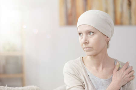 Close-up of a lonely, weak and sick woman with cancer sitting at home alone