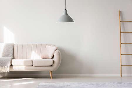 Beige bank met kussen en deken tegen de muur met kopie ruimte in platte interieur met ladder en lamp Stockfoto