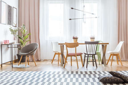 Dark cushions on patterned carpet and wooden chairs at dining table with heathers in bright flat interior with pink drapes Stock Photo - 97044753