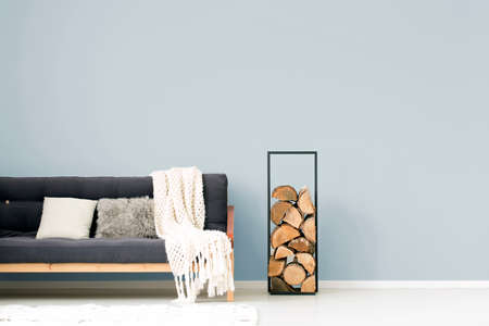 White blanket and pillows on wooden dark sofa next to logs of woods in living room interior Stock Photo