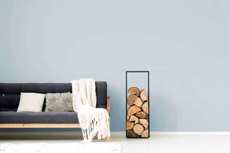 Witte deken en kussens op houten donkere bank naast logboeken van hout in woonkamerbinnenland