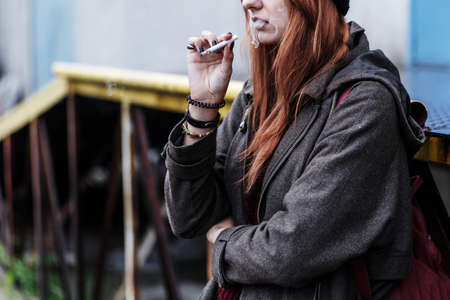 Cropped photo of a ginger teenager smoking a cigarette outside