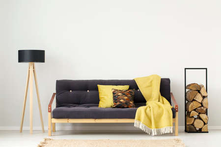Black sofa with yellow blanket between logs of wood and lamp in apartment interior with copy space