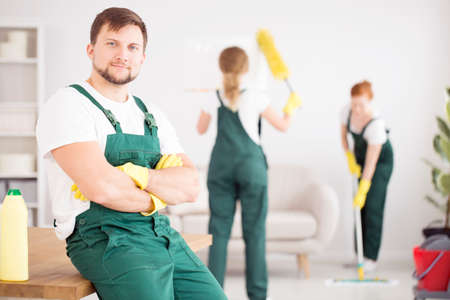 Smiling cleaner in green overalls and yellow gloves in the flat cleaned by a cleaning crew