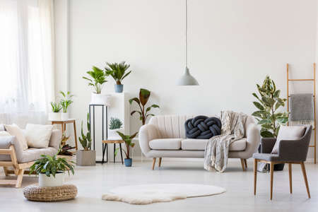 White fur and pouf in bright living room interior with settee under grey lamp near armchair and plants