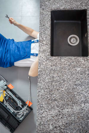 High angle of handyman on the floor with toolbox repairing black sink drain