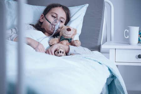 Dziecko z mukowiscydozą leżące w szpitalnym łóżku z maską tlenową i pluszową zabawką