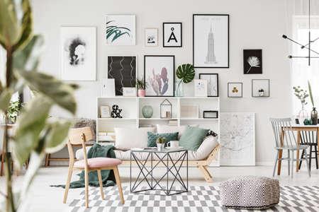 Gedessineerde poef, houten stoel en tafel op tapijt in modern plat interieur met bank tegen de muur met posters