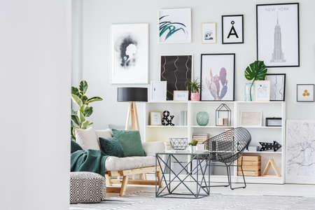 Galerij van posters boven kast in appartement interieur met cactus op tafel in de buurt van beige sofa en zwarte fauteuil Stockfoto