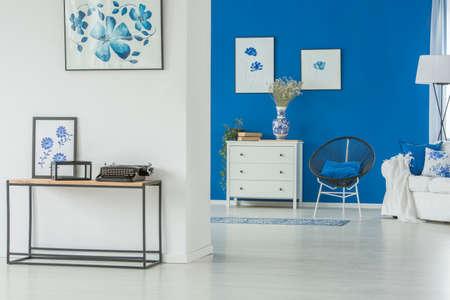 Machine à écrire et affiche sur une table en bois dans un salon spacieux et bleu avec une chaise à côté d'un placard blanc avec des fleurs
