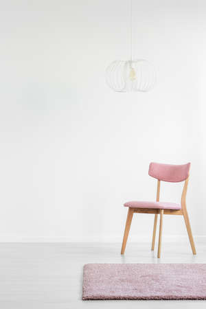 Pink wooden chair and carpet in empty white interior with copy space on the wall