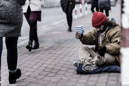 Hopeless beggar asking for food while sitting on the sidewalk between pedestrians Stock Photo