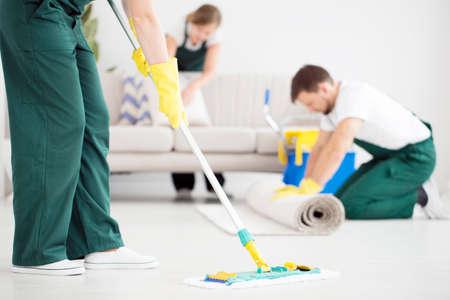 Reiniger in groene overall die de vloer schoonmaakt met een dweil in een lichte flat Stockfoto