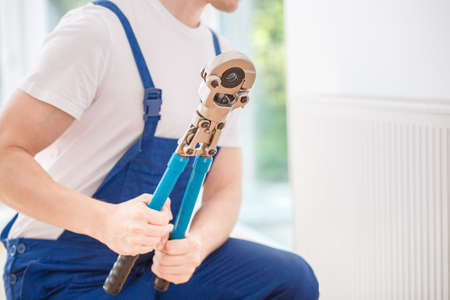 Close-up of handyman in blue overalls holding a hydraulic key