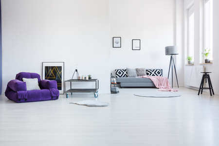 Purple armchair next to industrial table in spacious living room interior with black stool and patterned cushions on the sofa Stockfoto