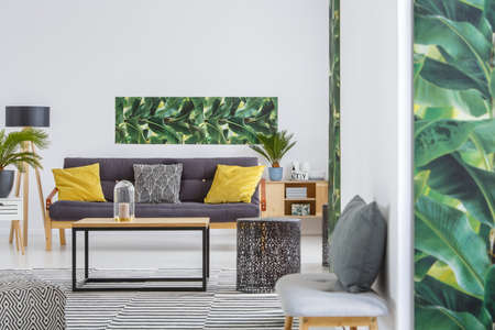 Leaves poster on the wall above couch with yellow pillows in spacious living room interior with table