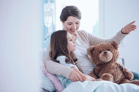 Ältere Schwester , die sich einem kranken Kind in einem Krankenhausbett mit Teddybären liegt Standard-Bild