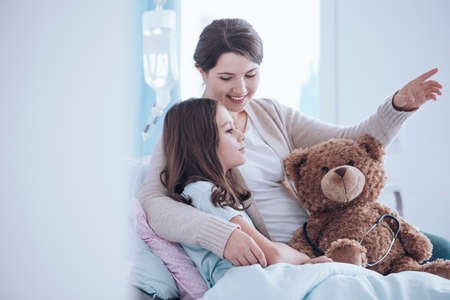 Older sister taking care of a sick child lying in a hospital bed with teddy bear Stockfoto