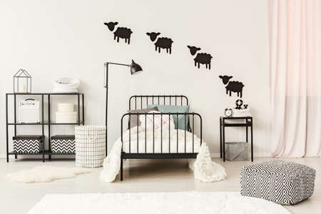 Patterned pouf near black bed with white bedsheets in teenagers bedroom with sheep stickers on the wall