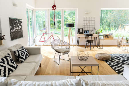 Corner couch with pillows and table in spacious scandi living room with workspace and bike