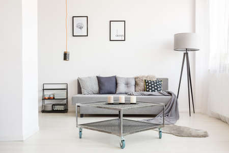 Handmade lamp above metal table with candles in modern living room interior with grey settee against a wall with posters