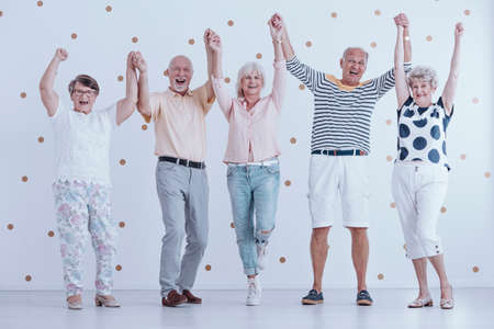 Excited elders holding hands in the air and welcoming new year together Reklamní fotografie - 94924080