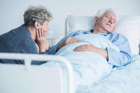 Bezorgde vrouw die voor haar zieke echtgenoot zorgt tijdens een bezoek in het ziekenhuis