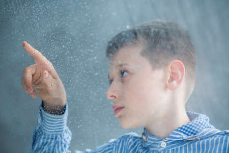 Photo through the window of autistic child counting raindrops