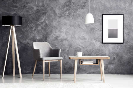 White lamp above wooden table next to grey armchair in living room interior with poster on concrete wall Archivio Fotografico