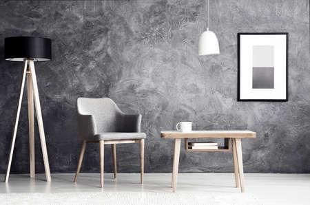 Lampe blanche au-dessus d'une table en bois à côté d'un fauteuil gris à l'intérieur du salon avec affiche sur mur en béton