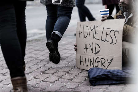 Pedestrians on the sidewalk and homeless and hungry pauper holding a sign