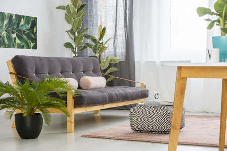 Patterned pouf and palm next to a dark, wooden settee in bright living room interior with pastel cushions Stock Photo